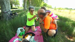 Grand parents enjoying picnic on summer holidays with grand daughter