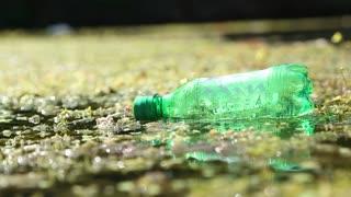 Green plastic bottle on wet floor.