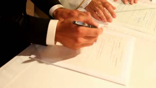Groom signing his name on wedding prenuptial agreement at church