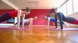 Group of attractive women doing yoga on rubber mats in hall
