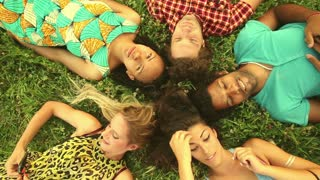 Group of five happy friends forming a circle with their heads laying back on grass, laughing and enjoying, graded
