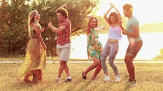 Group of five happy friends having fun dancing at sunset in summer, graded