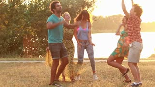 Group of five happy friends having fun dancing at sunset in summer