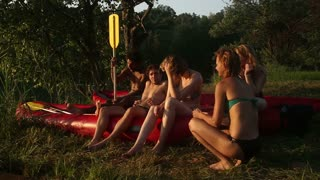 Group of five young friends resting in nature after riding a canoe, talking and laughing