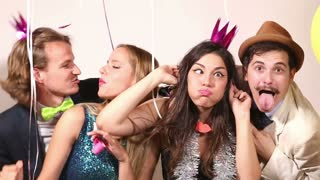 Group of four friends making funny faces in party photo booth