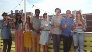 Group of multi-ethnic friends standing at rooftop and toasting