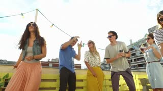 Group of people having fun dancing on the rooftop terrace