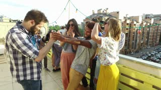 Group of people taking photos while musician playing guitar on rooftop terrace