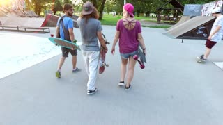 Group of three skateboarders hanging out in the skatepark