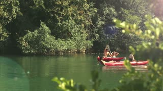 Group of young adults having fun in a canoe on beautiful Mreznica river, graded