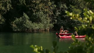Group of young adults having fun in a canoe on beautiful Mreznica river