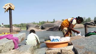 HAMPI, INDIA - 28 JANUARY 2015: Close view of woman and child washing clothes.