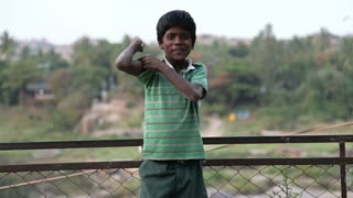 HAMPI, INDIA - 28 JANUARY 2015: Cute indian boy showing his hand muscles to the camera