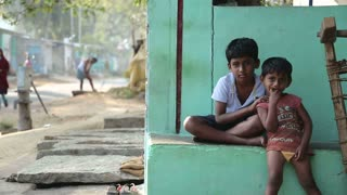 HAMPI, INDIA - 28 JANUARY 2015: Cute indian boys sitting in front of green painted house in Hampi.