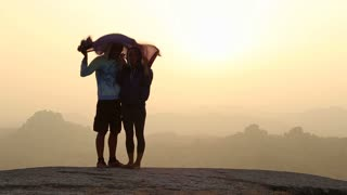 HAMPI, INDIA - 28 JANUARY 2015: Hugged woman and man standing on the mountain during beautiful sunset