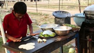HAMPI, INDIA - 28 JANUARY 2015: Indian boy preparing food on the street in Hampi.
