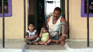 HAMPI, INDIA - 28 JANUARY 2015: Indian grandfather sitting at the door entrance with two grand children.