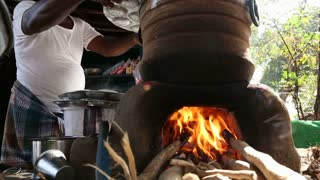 HAMPI, INDIA - 28 JANUARY 2015: Indian man cooking on open fire stove.