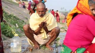 HAMPI, INDIA - 28 JANUARY 2015: Indian man doing bath ceremony on the riverbank in Hampi
