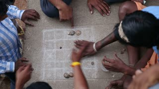 HAMPI, INDIA - 28 JANUARY 2015: Indian men playing board game on the streets of Hampi.