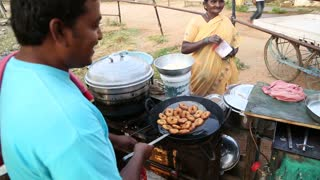 HAMPI, INDIA - 28 JANUARY 2015: Indian people preparing food on the street in Hampi.