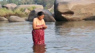 HAMPI, INDIA - 28 JANUARY 2015: Indian woman standing in the river and taking bath.
