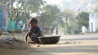 HAMPI, INDIA - 28 JANUARY 2015: Little child picking up dried leaves in a pot on a street in Hampi.
