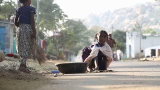 HAMPI, INDIA - 28 JANUARY 2015: Little children picking up dried leaves in a pot on a street in Hampi.