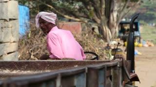 HAMPI, INDIA - 28 JANUARY 2015: Man in pink shirt slowly driving backwards little traktor.