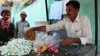 HAMPI, INDIA - 28 JANUARY 2015: Man selling flower necklaces at temple entrance.