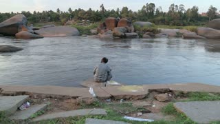 HAMPI, INDIA - 28 JANUARY 2015: Man sitting on the riverside and looking at river.