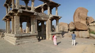 HAMPI, INDIA - 28 JANUARY 2015: Man taking picture of woman in front of temple ruins in Hampi.