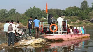 HAMPI, INDIA - 28 JANUARY 2015: Men boarding a big white bag and a motorcycle on the river boat.