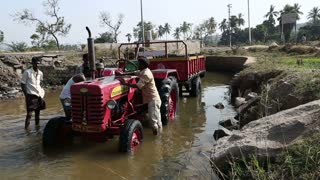 HAMPI, INDIA - 28 JANUARY 2015: Men washing tractor parked in a river.