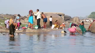 HAMPI, INDIA - 28 JANUARY 2015: People having bath on the Tungabhadra river in Hampi.