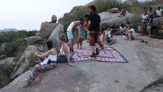 HAMPI, INDIA - 28 JANUARY 2015: People sitting on the large stones in Hampi.