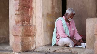HAMPI, INDIA - 28 JANUARY 2015: Portrait of indian man sitting at the entrance in one of the temples in Hampi.