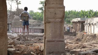 HAMPI, INDIA - 28 JANUARY 2015: School boy standing on the ruins of temple in Hampi.