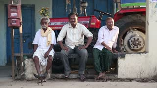 HAMPI, INDIA - 28 JANUARY 2015: Three indian adult men sitting in front of house and posing.
