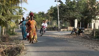 HAMPI, INDIA - 28 JANUARY 2015: Three women walking down the road in Hampi while two men on motorcycle pass by