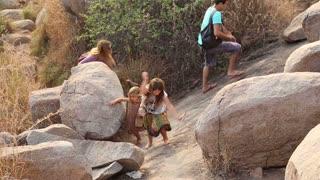 HAMPI, INDIA - 28 JANUARY 2015: Two girls climbing between large stones in Hampi.
