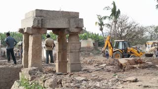 HAMPI, INDIA - 28 JANUARY 2015: View of people, digger and truck at the ruins on one of the temples in Hampi