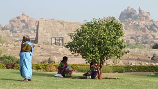 HAMPI, INDIA - 28 JANUARY 2015: View of three women on the grass, two sitting under the tree, third standing.