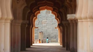 HAMPI, INDIA - 28 JANUARY 2015: View through gateway of curious children and woman looking at temple.