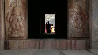 HAMPI, INDIA - 28 JANUARY 2015: View through the dark corridor, women walking at its end.