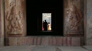 HAMPI, INDIA - 28 JANUARY 2015: View through the dark corridor, women walking at its end.