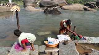 HAMPI, INDIA - 28 JANUARY 2015: Woman and child washing clothes, man washing elephant at the river.