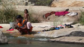 HAMPI, INDIA - 28 JANUARY 2015: Woman at the riverbank and washing clothes with children playing around her.