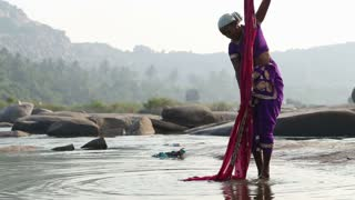 HAMPI, INDIA - 28 JANUARY 2015: Woman standing on riverbank cleaning her sari in river.