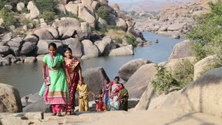 HAMPI, INDIA - 28 JANUARY 2015: Women climbing up through large rocks along river.